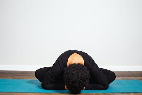 Woman in Black Long Sleeve Shirt and Blue Pants Lying on Blue Yoga Mat