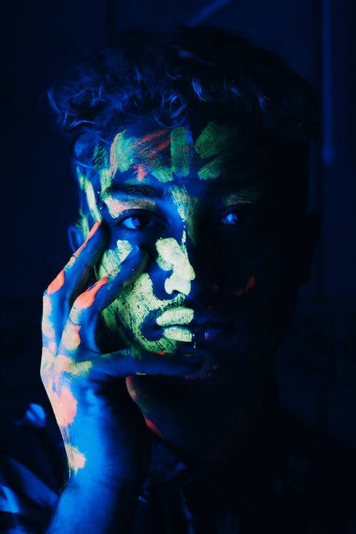 Serious ethnic guy touching face covered with fluorescent paints