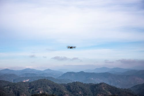 White and Black Airplane Flying over the Mountains