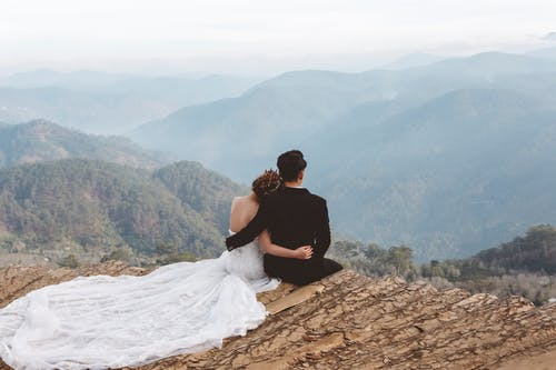 Man and Woman Sitting on Brown Rock