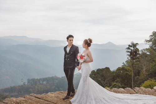 Man in Black Suit and Woman in White Wedding Dress Kissing on Brown Rock Formation during