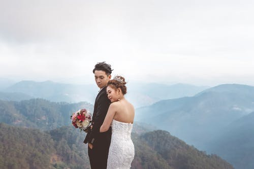 Man and Woman Standing on Top of Mountain