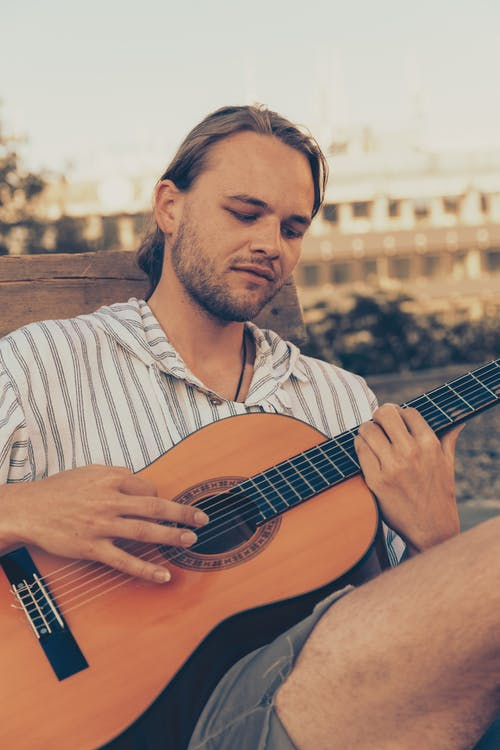 Bearded male musician in casual summer clothes sitting on bench in park and playing acoustic guitar
