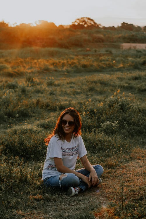 Full body of cheerful young woman in casual closing sitting on grass with legs crossed and looking away with bright toothy smile while resting in meadow at sunset