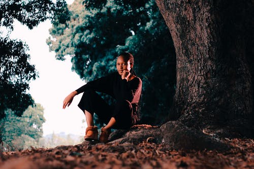Pensive young African American female in casual clothing looking at camera while sitting under big tree with hand at cheek