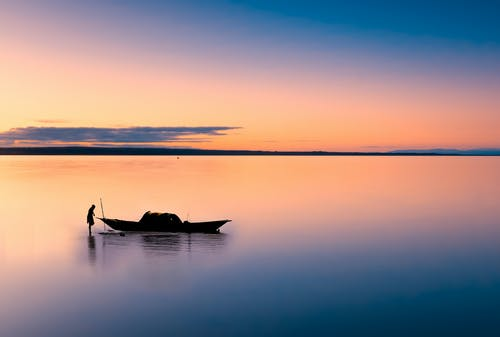 Vibrant multi colored sky above silhouette of anonymous fisher standing in still shallow water with boat near