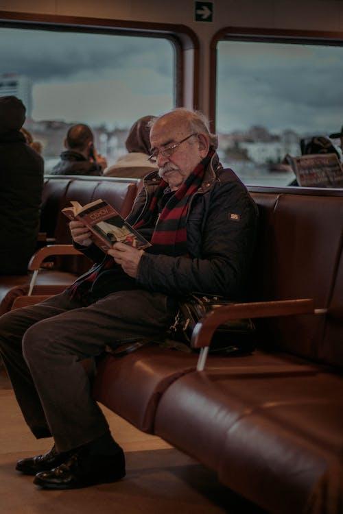 Senior man reading book in bus terminal