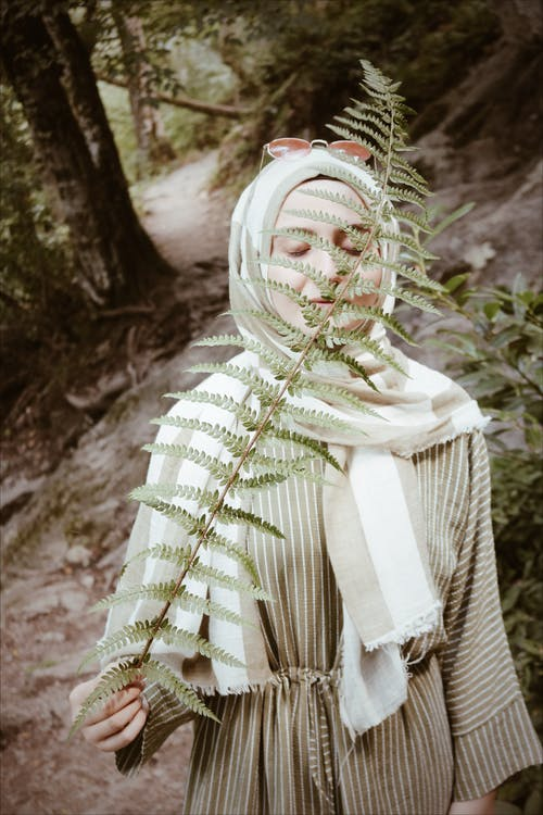 Woman sniffing leaf blade of fern