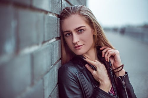 Serious young woman in leather jacket with sandy hair and makeup looking at camera while adjusting collar and leaning to brick wall