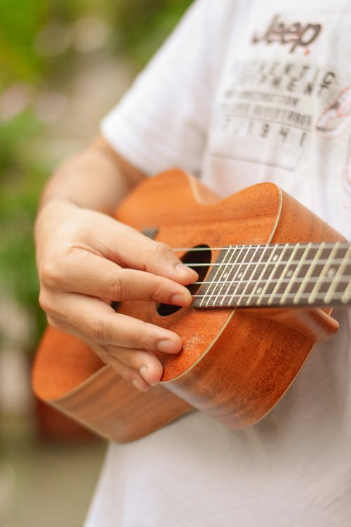 Crop person practicing to play ukulele
