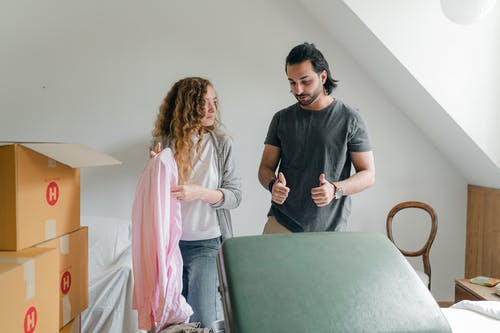 Positive young couple in casual clothes packing belongings into carton boxes and discussing new home while moving in together