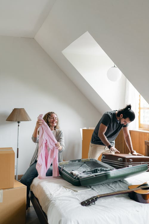 Full body happy young couple packing suitcases and carton boxes while preparing to move into new apartment in empty bedroom on sunny day