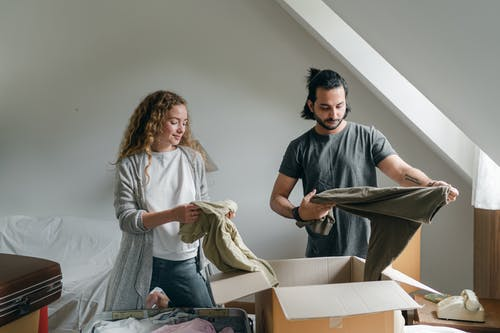 Content couple unpacking clothes during relocation