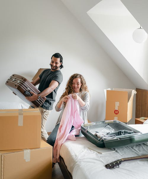 Cheerful couple packing boxes and suitcases