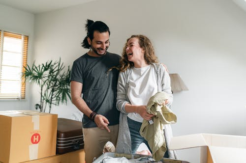 Excited couple unpacking boxes in new apartment