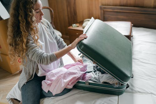 Focus woman packing suitcase on bed