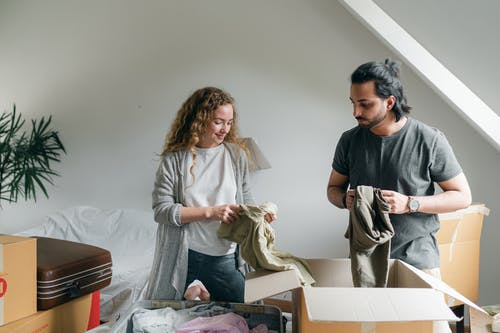 Content young couple in casual outfit standing in new modern bedroom and unpacking boxes together after relocation into new apartment