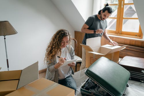 Couple packing belongings into suitcases and carton boxes