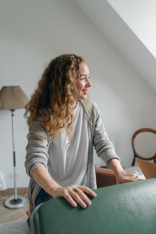 Happy woman with suitcase in bedroom