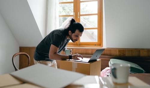 Side view of focused bearded male in casual outfit with cup of hot drink browsing laptop while packing stuff into carton boxes