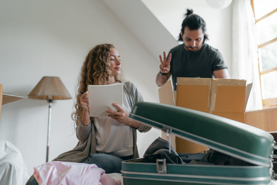 Focused couple packing stuff before moving out