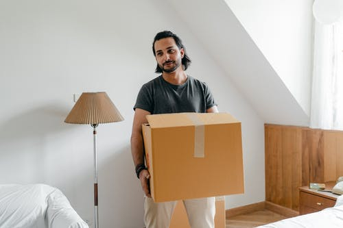 Cheerful young bearded male in casual wear carrying cardboard container in sunny bedroom while moving into new apartment
