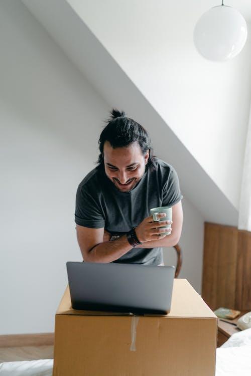 Happy man using laptop near carton box