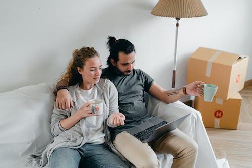 Bonding couple browsing laptop after packing carton boxes