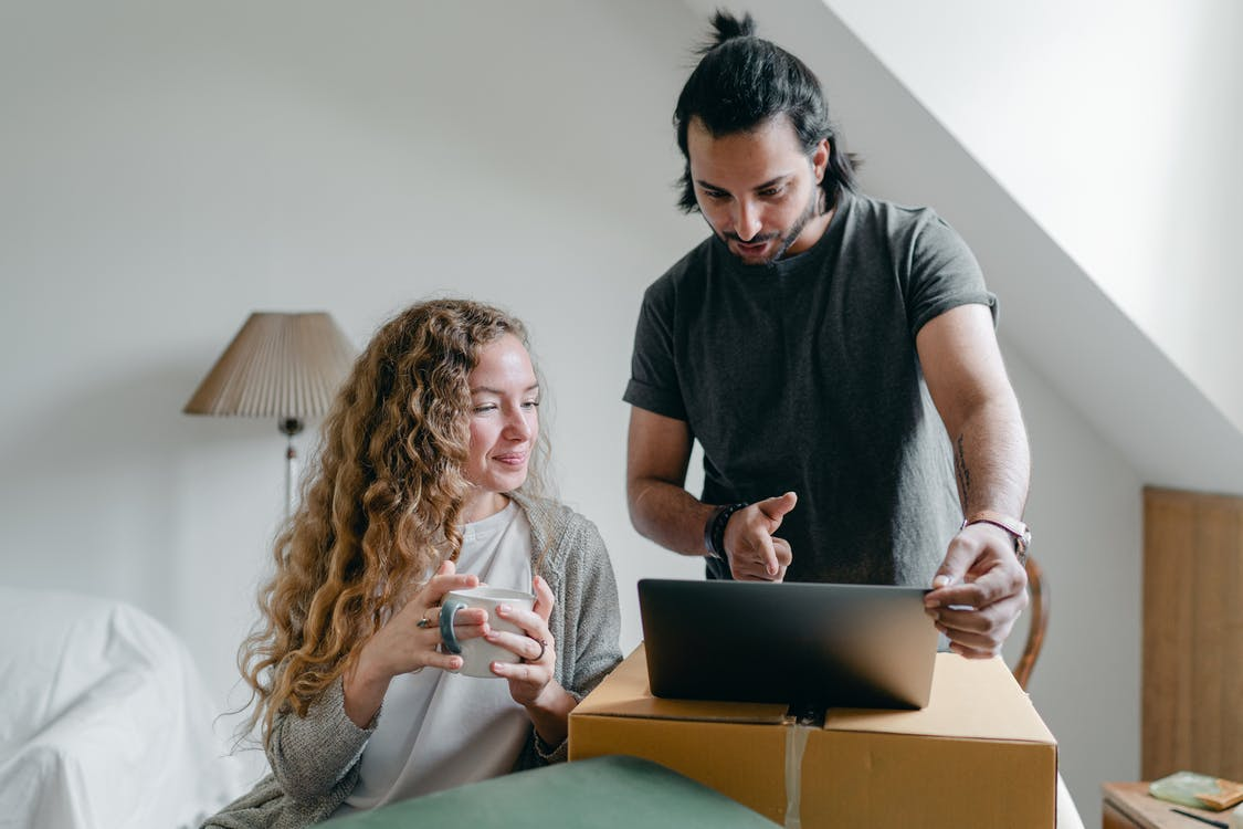 Positive happy young couple in casual clothes packing belongings into carton box and using laptop in living room near window