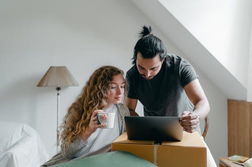 Concentrated young couple in casual outfit browsing netbook and packing stuff into carton boxes and suitcases to move out