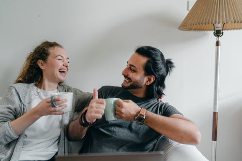 Positive girlfriend in casual wear looking at content ethnic man in smart watch while sitting on cozy sofa with cups of hot beverage and looking at each other
