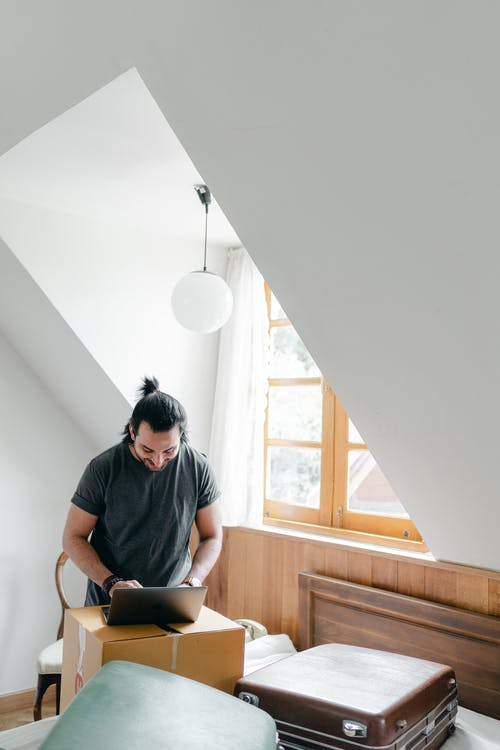 Ethnic man browsing internet on attic style room in house