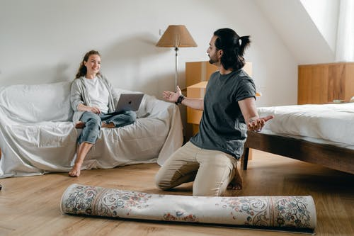 Happy woman with laptop looking at ethnic man with carpet