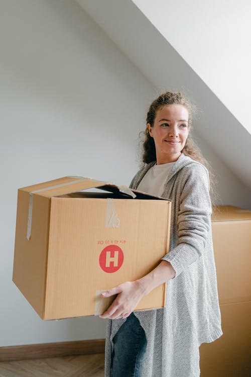 Smiling woman in cardigan holding cardboard box at home