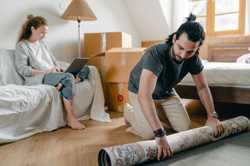 Woman with laptop and ethnic boyfriend laying carpet in flat