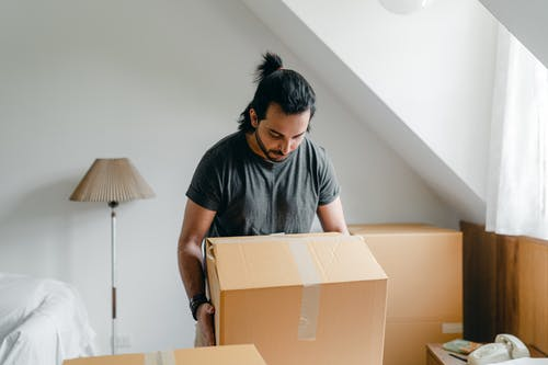 Ethnic guy picking up cardboard box in house