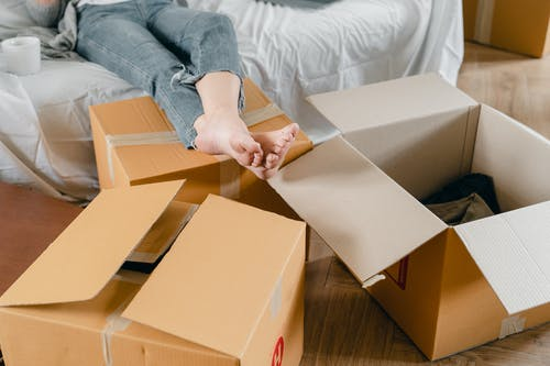 Crop unrecognizable slim woman sitting on sofa near cardboard boxes