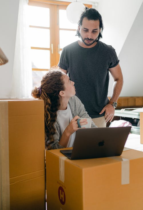 Girlfriend with laptop interacting with ethnic man in new apartment