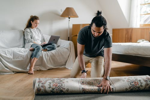 Ethnic man laying rug on floor and girlfriend using laptop