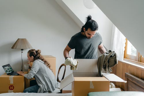 Woman browsing internet on laptop and boyfriend doing housework