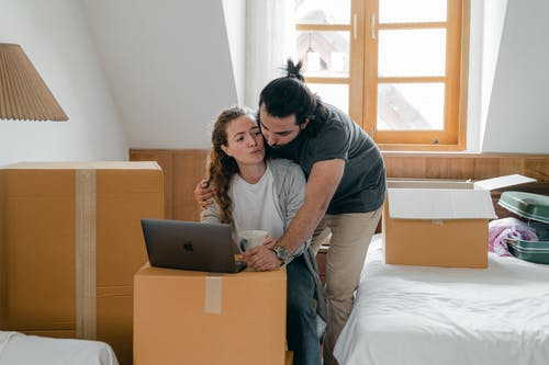 Multiracial couple embracing while using laptop in attic style bedroom
