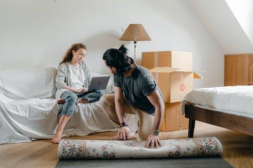 Ethnic boyfriend laying carpet on parquet near woman with laptop