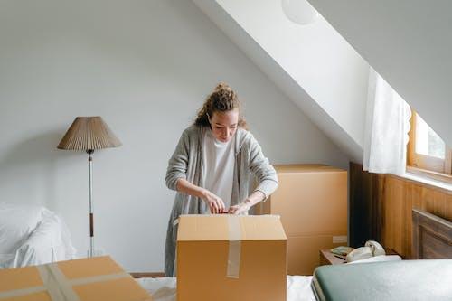 Calm woman unpacking big box in light living room
