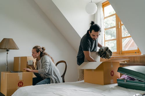 Ethnic boyfriend unpacking box while woman using laptop at home