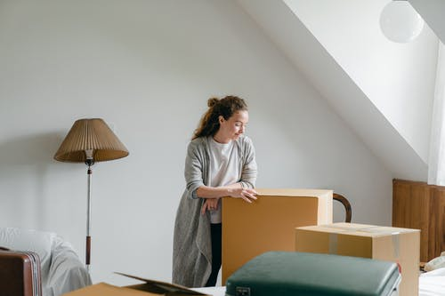Ponder woman standing leaned on big box at home