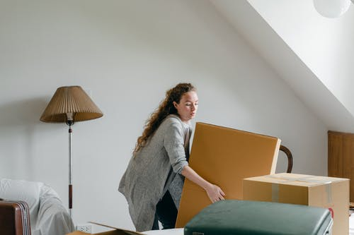 Slim female in cardigan taking big rectangular cardboard box while standing near suitcases and sofa in attic style living room in daylight