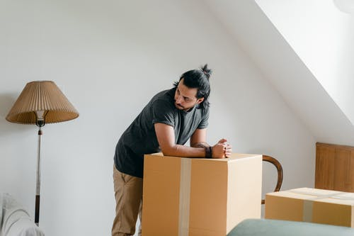 Ponder ethnic guy in smart watch leaned on box