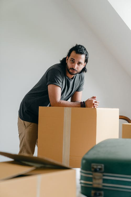 Thoughtful ethnic male in casual clothes standing leaned on big square cardboard box near suitcase and looking at camera in apartment