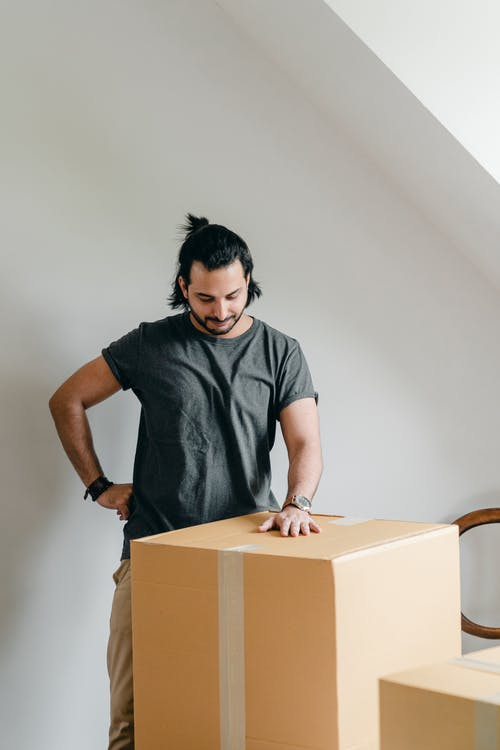 Smiling ethnic man in wristwatch touching cardboard box in house