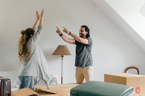 Cheerful man showing at unrecognizable girlfriend standing with raised hands